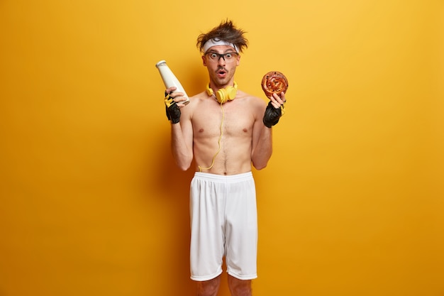 Fitness, esporte, perda de peso e conceito de dieta. fisiculturista atordoado posa com garrafa de leite e pão saboroso e apetitoso, usa shorts brancos e luvas esportivas e fica de pé contra a parede amarela
