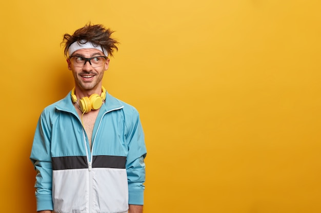 Fitness esportivo cara de bom humor, olha para o lado com motivação, gosta de exercícios e esportes, ouve música em fones de ouvido durante o treino, vestido com roupa ativa, copie espaço na parede amarela