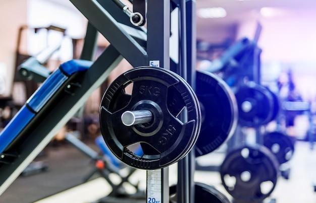 Fitness exercício halteres de equipamentos no ginásio de esportes. placas de barra pretas no centro de ajuste esportivo. fechar-se