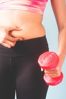 Fitness fêmea em calças pretas e sutiã de esporte rosa segurando dumbbell vermelho