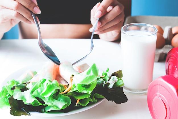 Fitness feminino comendo salada fresca e leite