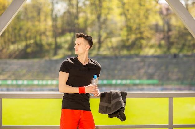 Fitness homem beber água de garrafa. sedento atleta tendo refresco frio bebida após exercício intenso