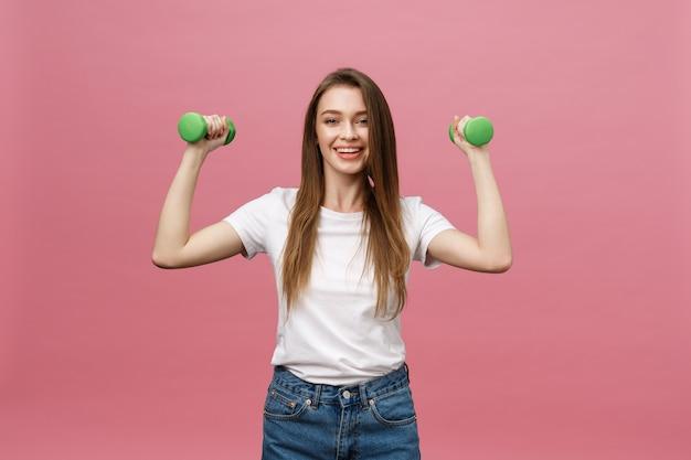 Fitness, jovem mulher com halteres no fundo do estúdio