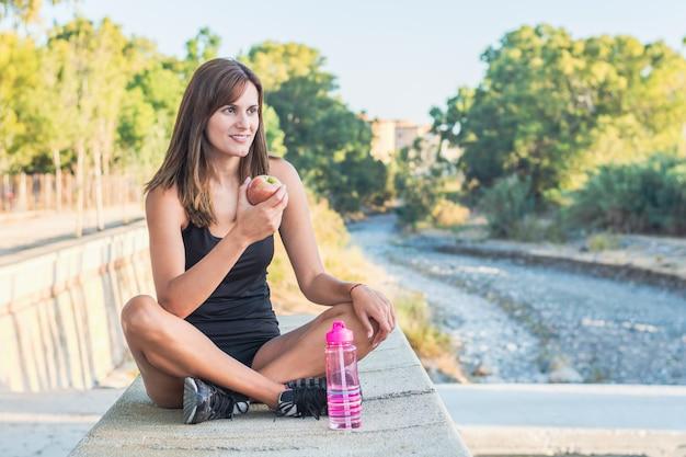 Fitness jovem mulher comendo uma maçã depois de treino em um parque