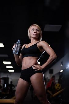 Fitness menina beber água de uma garrafa de plástico depois de um treino
