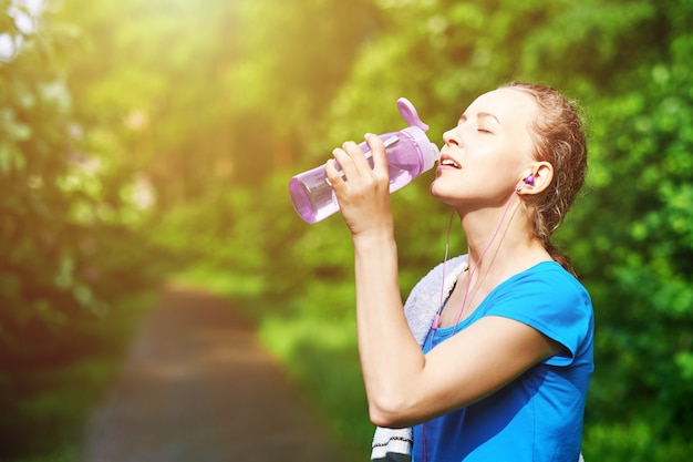 Fitness mulher bebendo água após a execução de treinamento no parque de verão