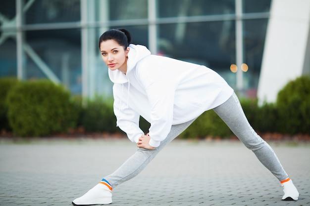 Fitness, mulher jovem e bonita fazendo exercícios no parque