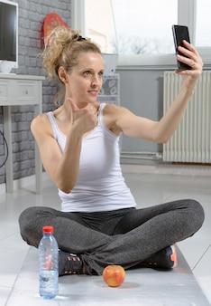 Fitness mulher tirando foto com o telefone dela, após o exercício