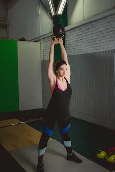 Fitness mulher treinando pelo kettlebell. jovem cabida que faz o exercício do crossfit.