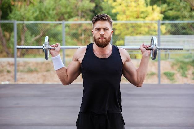 Fitness musculoso barbudo treino de homem bonito com barra ao ar livre