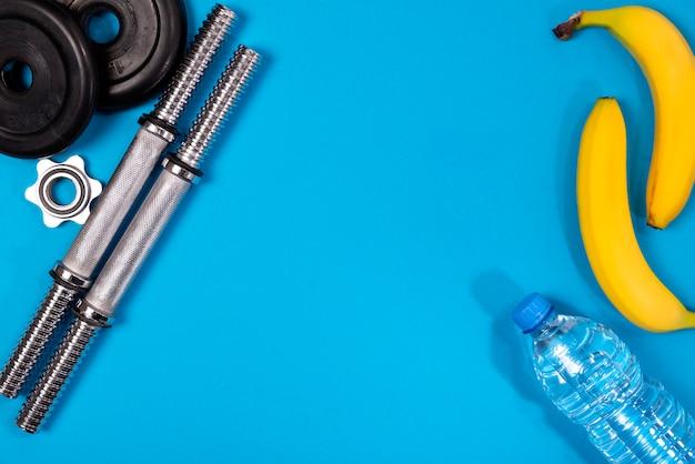 Fitness ou musculação. equipamento desportivo, banana, garrafa de água, barra, haltere, vista superior