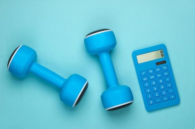 Fitness, perda de peso ainda vida. contagem de calorias. calculadora e halteres em pastel azul