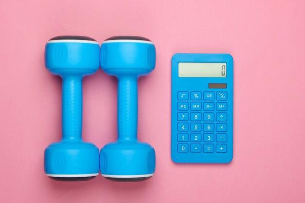 Fitness, perda de peso ainda vida. contagem de calorias. calculadora e halteres em um pastel rosa