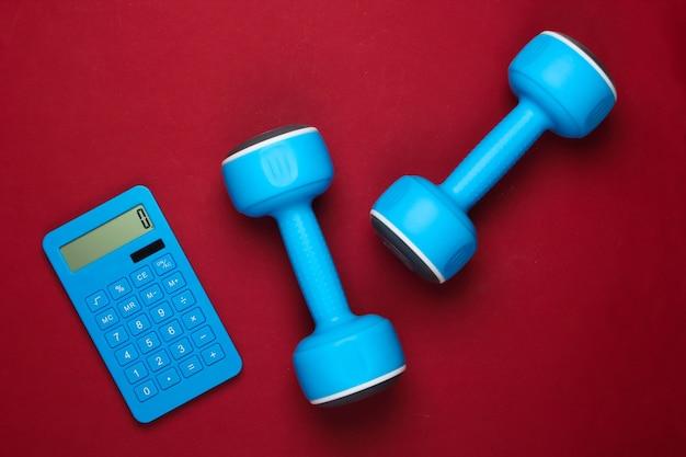 Fitness, perda de peso ainda vida. contagem de calorias. calculadora e halteres em vermelho. minimalismo