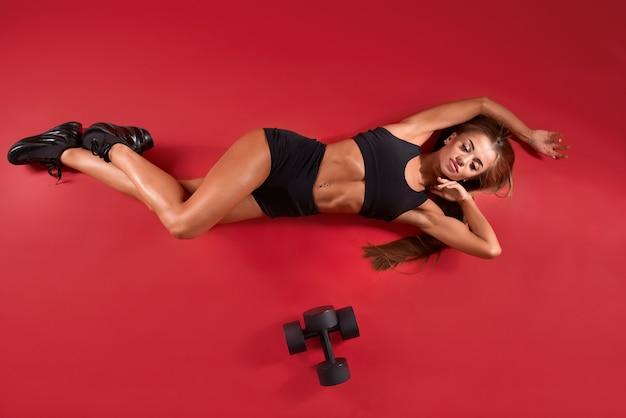 Fitnesswoman deitada perto de halteres no chão vermelho