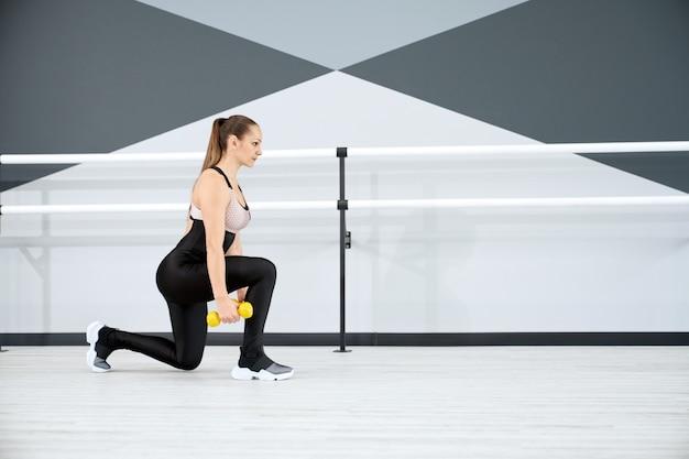 Fitnesswoman praticando estocadas usando halteres