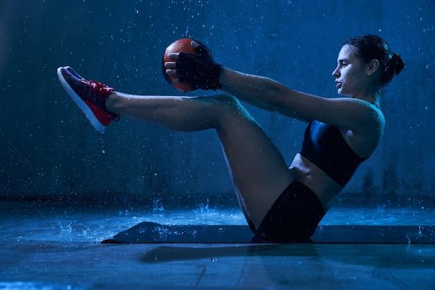 Fitnesswoman treinando abdominais usando uma pequena bola de chuva