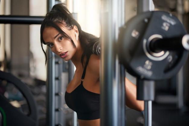 Fitnesswoman treinando em uma máquina de ferreiro