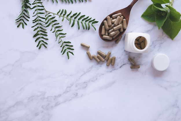 Fitoterapia em cápsulas na colher de madeira com folha verde natural em mármore branco