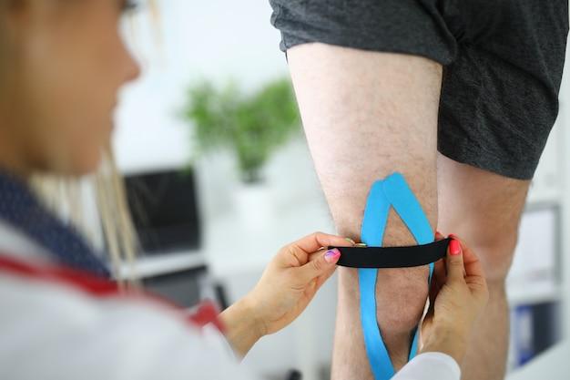 Fixação de fita cinesio na perna do paciente.