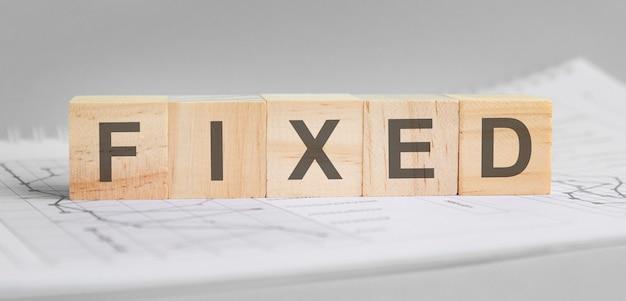 Fixed é escrito em blocos de madeira leves. a palavra está localizada em uma folha com tabelas e gráficos. conceito de negócios. fundo cinza