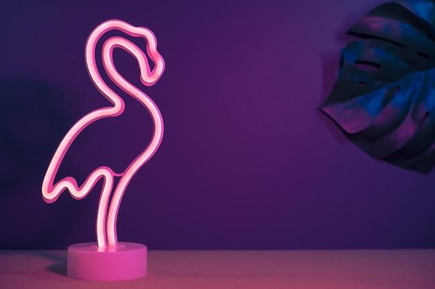 Flamingo-de-rosa de verão e folha de monstera com luz rosa e azul neon