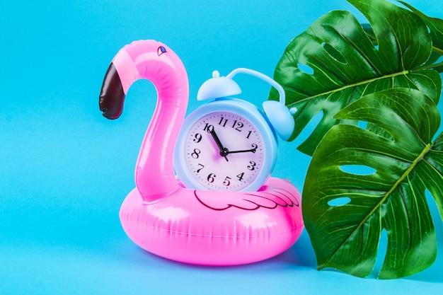 Flamingo inflável rosa sobre fundo azul com folhas de monstera e relógio.