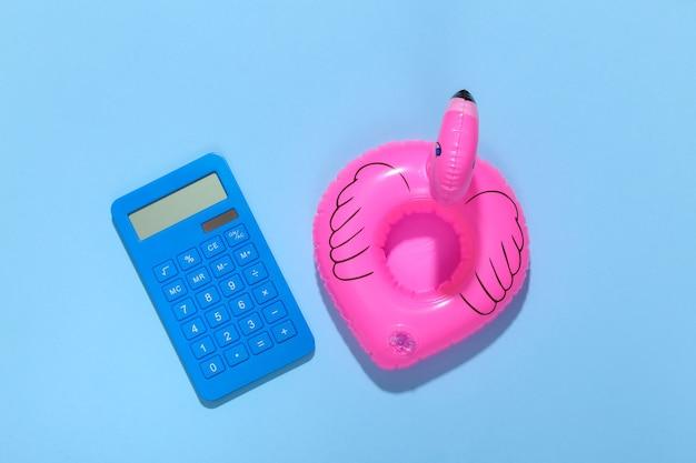 Flamingo rosa inflável com calculadora sobre fundo azul ensolarado. conceito de férias de verão. minimalismo. vista do topo.