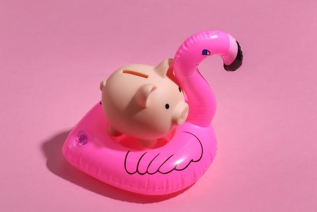 Flamingo rosa inflável e cofrinho em fundo rosa ensolarado. conceito de férias de verão. minimalismo