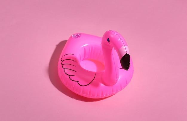 Flamingo rosa inflável sobre fundo rosa ensolarado. conceito de férias de verão. minimalismo