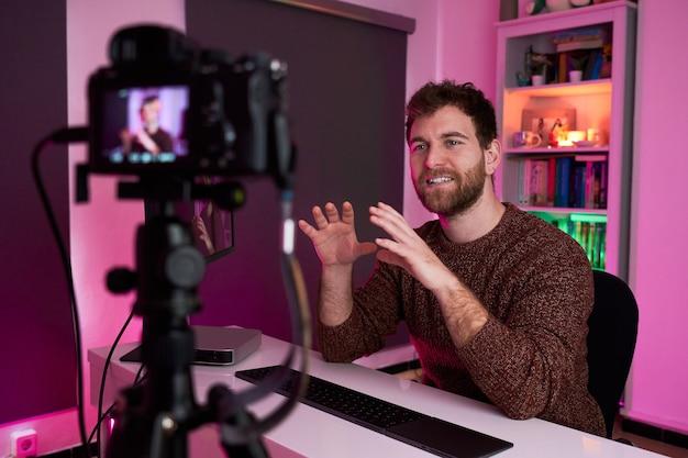Flâmula de homem transmitindo ao vivo gesticulando com as mãos para a câmera
