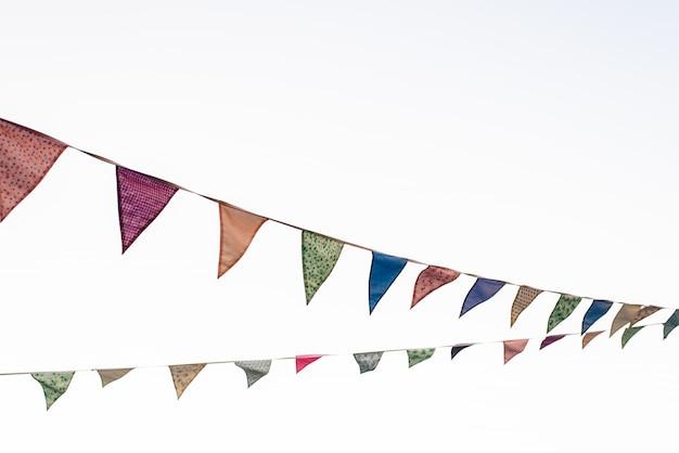 Flâmulas com fundo de céu azul e cores pálidas, pendurado em uma corda, cruzando a imagem durante um evento ao ar livre