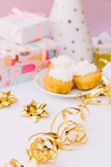 Flâmulas de redemoinho na frente do cupcake de desfoque; presentes e chapéu de festa na mesa branca