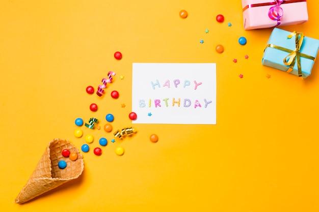 Flâmulas e pedras preciosas no waffle com feliz aniversário em papel contra o fundo amarelo