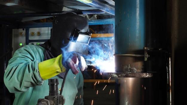 Flange de solda da tubulação de aço do trabalhador industrial, uma soldadura de faísca.