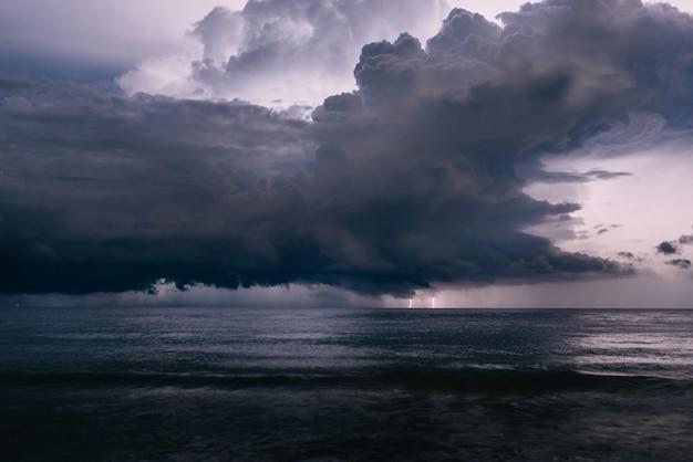Flash de relâmpago no céu noturno sobre o mar, tempestade