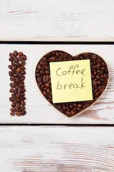 Flat lay adoro o conceito de pausa para o café. grãos de café em forma de coração. madeira branca na superfície.