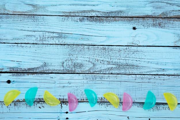 Flat lay azul placa de madeira com limões de plástico coloridos