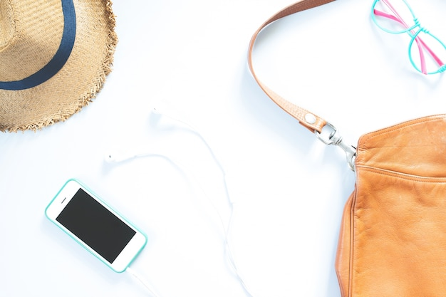 Flat lay colagem de acessórios femininos com chapéu, bolsa, óculos de moda, telefone celular e fone de ouvido no fundo branco.