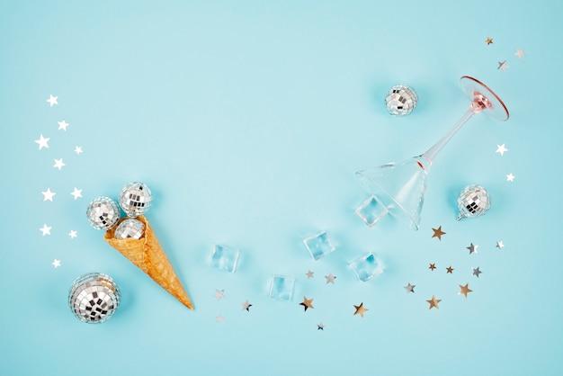 Flat lay com bolas de discoteca no cone, cubos de gelo, copo de coquetel