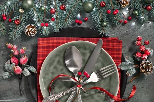 Flat lay com decorações de natal em verde e vermelho com bagas geadas, bugigangas, pratos e louças