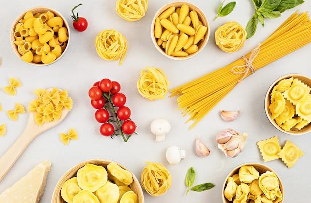 Flat lay com diferentes tipos de massa tradicional italiana. penne, tagliatelle, fusilli, farfalle, espaguete e ingredientes para cozinhar. conceito tradicional da culinária italiana. vista do topo
