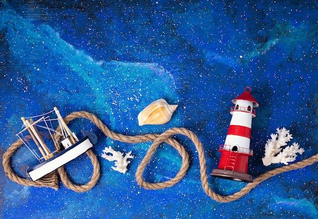 Flat lay com férias de verão em símbolos do lado do mar. farol, barco, corda de marinheiro. copiar espaço, vista superior