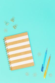 Flat lay com papelaria para escola, educação. caderno fechado na primavera, lápis, clipes de metal dourado para papel.