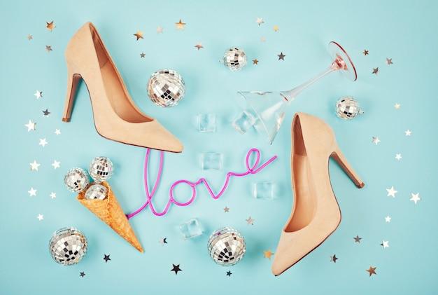 Flat lay com sapatos femail, bolas de discoteca, cubos de gelo, copo de coquetel e confetes.