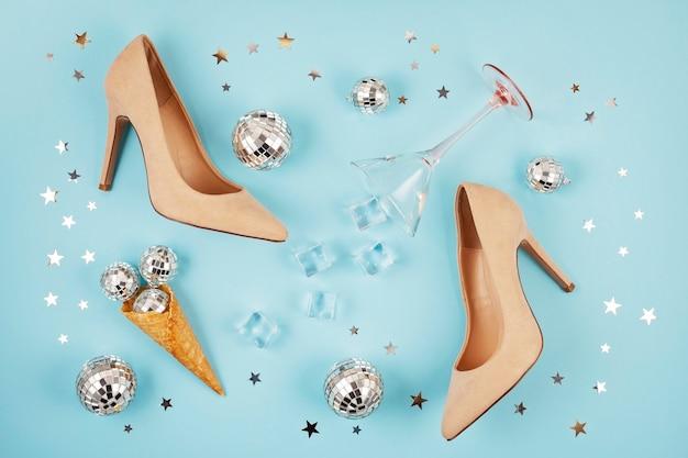 Flat lay com sapatos femail, bolas de discoteca no cone e copo de coquetel