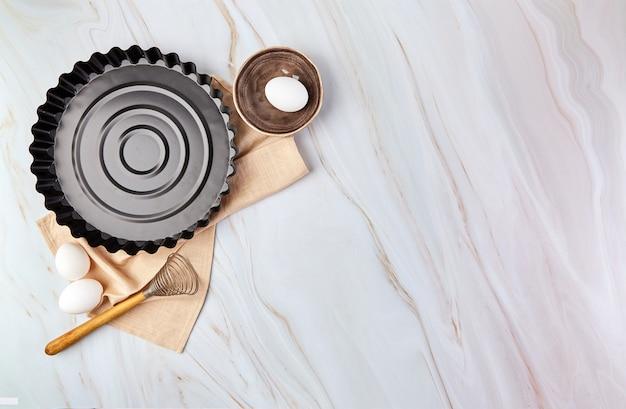 Flat lay com utensílios de cozimento e ingredientes de cozinha para tortas, biscoitos, massa e pastelaria em mármore.