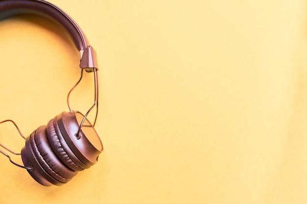 Flat lay concept: fones de ouvido em amarelo pastel