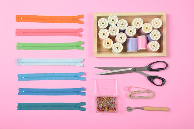 Flat lay de material de costura contém a tesoura, fita métrica, zíper e rolos de linha.