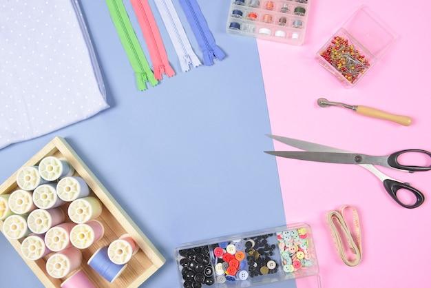 Flat lay de material de costura contém os rolos de tecidos, tesoura, zíper, pino e linha.